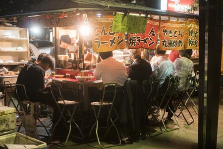 FUKUOKA, JAPAN - SEPTEMBER 29, 2017: People eating Yatai mobile food stall at night in Fukuoka, Kyushu, Japan