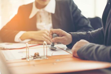 Geschäftshand, die Stempel auf ein Dokument, Abschluss aufstellt
