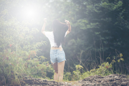 Young woman with windy messy hair backlit by sun selective focus toned image, sun flares Stock Photo