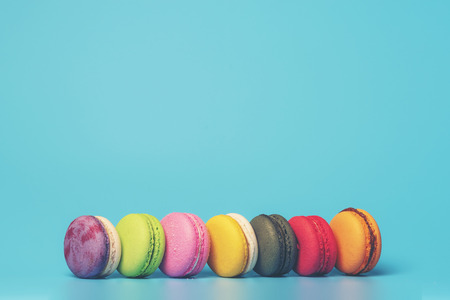 Cake macaron or macaroon on turquoise background from above, colorful almond cookies, pastel colors, vintage card