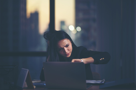 Tired woman at home office looking at her watch Stock Photo