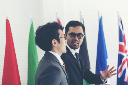 Asian businessman standing against national flags, business deal concept 写真素材