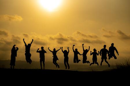 Schattenbild des glücklichen Geschäftsmenschenteams, das hohe Hände über Kopf in Sonnenuntergangshimmelabendzeithintergrund für Geschäftsteamarbeitskonzept und Freiheit macht