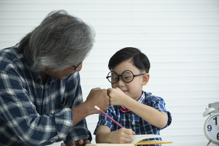 Older teachers are teaching students to do homework, education concept