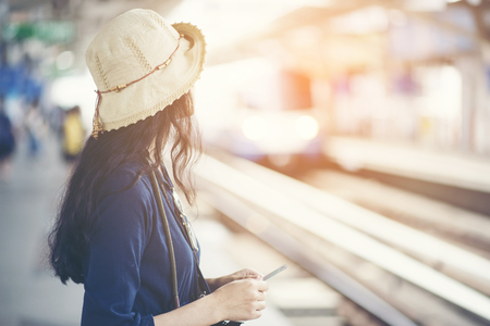 Asian girl waiting train at skytrain station for travel in the big city, lifestyle and transportation concept Stock Photo