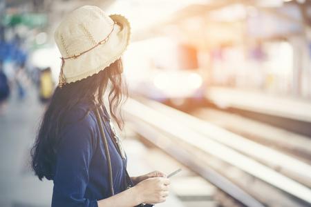 Azjatycka dziewczyna czeka na pociąg na stacji Skytrain na podróż w wielkim mieście, koncepcja stylu życia i transportu Zdjęcie Seryjne