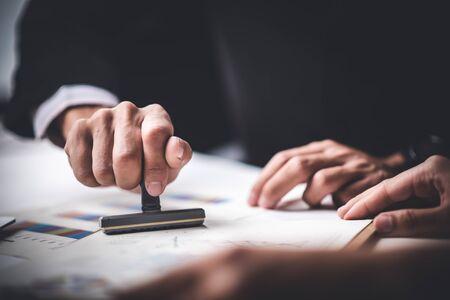 Close-up of a Person's Hand Stamping avec tampon approuvé sur le texte Document approuvé au bureau, formulaire de contrat papier Banque d'images