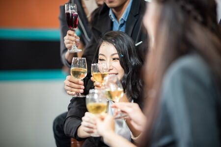 A group of business people holding a glass of champagne in a party to celebrate their success