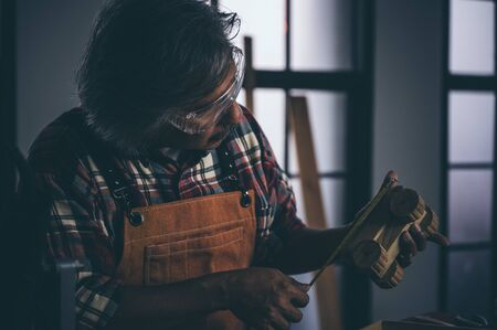old carpenter man working in carpenter studio