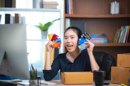 Jeune femme tenant une carte de crédit et utilisant un ordinateur portable. Concept d'achat en ligne