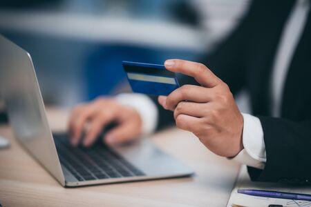 zakenman die met creditcard en laptop werkt