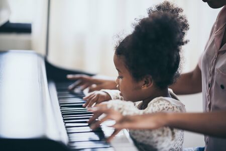 American African young pianist, teacher teaching girl kid student to play piano, Art of music education concept Standard-Bild
