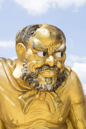 Antique statue of a Chinese monk with blue sky Stock Photo