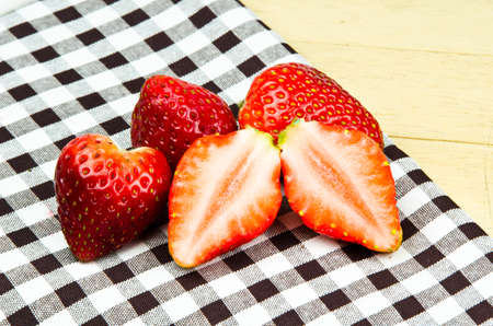 Fresh strawberries on fabric checker textile photo