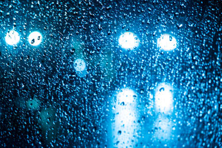 bubble level: beautiful drops of water on a glass street light at night. Stock Photo