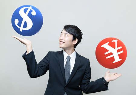 Asian businessman making comparison between a Dollar sign and a Yen (or Yuan) sign. 版權商用圖片