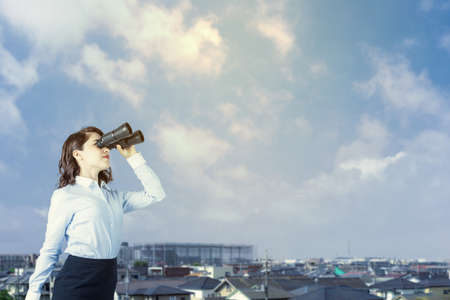 young woman holding binocular glasses. residential houses background.