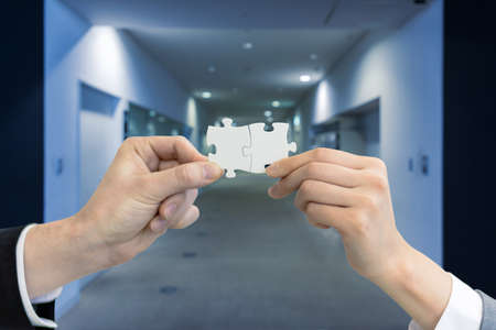 man and woman hand holding jigsaw puzzles, business matching concept Banque d'images
