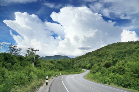 Lange und kurvenreiche Straße mit Wolken und blauer Himmel Standard-Bild - 39993058