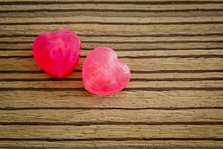 Heart shape sweet candy on the wooden background