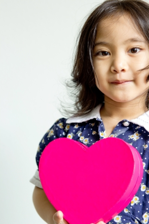 A little girl stands with a heart box