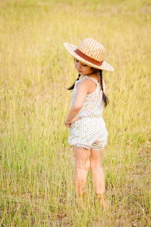 Little girl with sunhat in the field Stock Photo