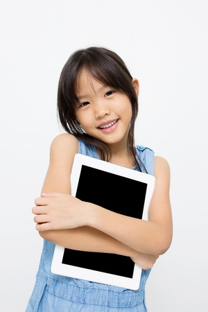 Happy Asian child with tablet computer photo