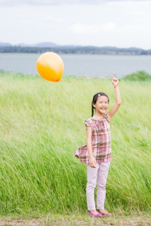 Little asian girl with orange balloon