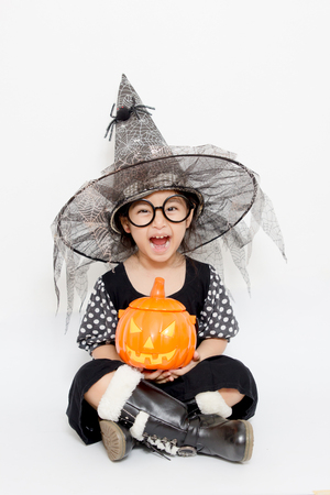 Surprise ni�o bruja feliz con la calabaza en traje de Halloween photo