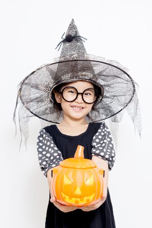 Surprise Happy witch child with pumpkin in Halloween dress photo