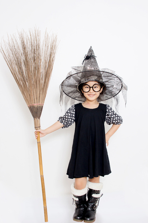 Asian witch child holding magic broom in Halloween dress photo
