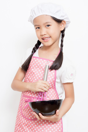Little Asian cute chef wearing pink apron Stock Photo