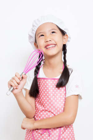 Little Asian cute chef wearing pink apron thinking action Stock Photo