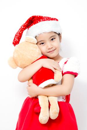 Little Asian girl huging bear doll on christmas isolated in white photo