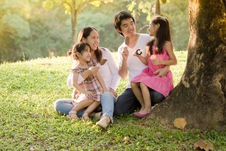Glückliche asiatische Familie mit Eis im Park