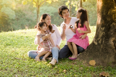 woman with ice cream: Happy Asian family with icecream in park