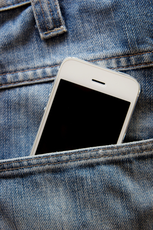 Close up of smartphone in pocket jeans photo