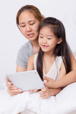 Little Asian child using tablet with mother photo