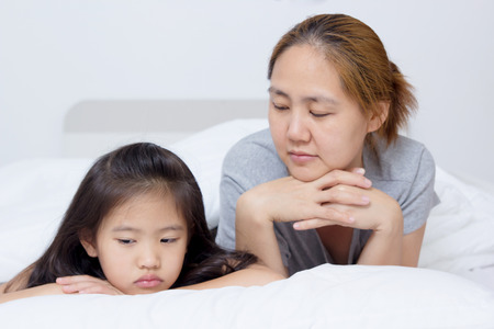 Portrait of unhappy Asian mother and daughter in bed time