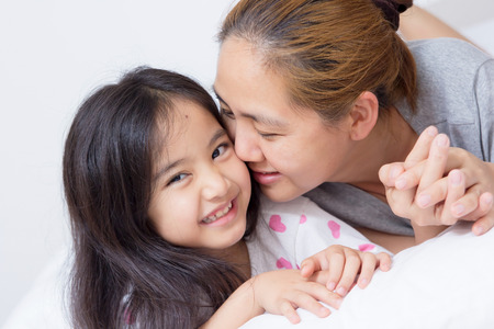 Portrait of happy Asian mother kissing daughter