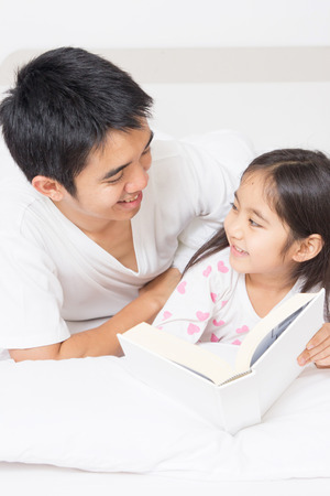Little Asian child reading a story book with father on the bed