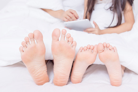 Family with tablet on bed showing their feet