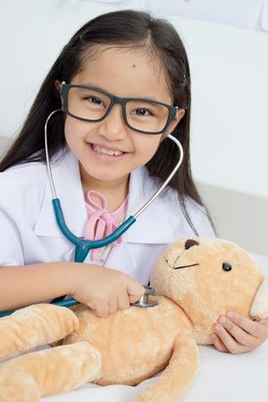 アジアの女の子は医者として聴診器とクマの人形で遊んで
