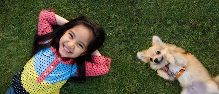Gelukkig Aziatisch meisje met haar hondje portret liggend op het gazon