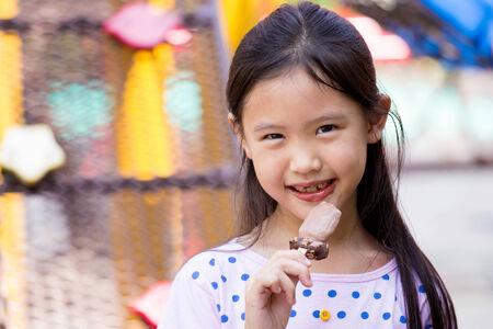 Little Asian cute child enjoy eating ice-cream near the playground photo