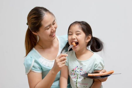 Asian mother feeding sausage to her daughter 스톡 콘텐츠