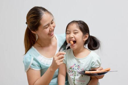 Asiatische Mutter Fütterung Wurst, um ihre Tochter