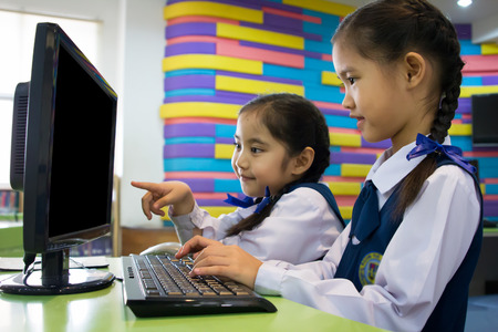 üniforma: Bilgisayarı kullanarak küçük sevimli Asyalı kız Stok Fotoğraf