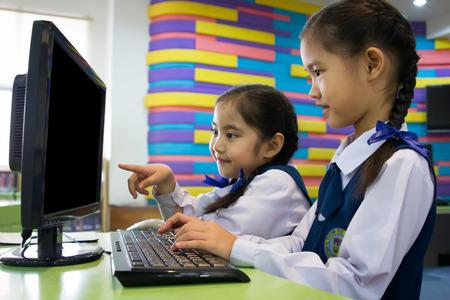uniformes: Niña asiática linda que usa la computadora Foto de archivo