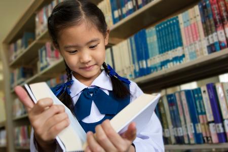niños estudiando: Pequeña estudiante asiático en biblioteca